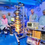 Fermilab engineers and Department of Atomic Energy visitors pause work to pose next to a 5-cell 650 MHz superconducting radio frequency cavity