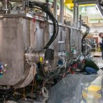 Technicians work on the half-wave resonator (HWR) at PIP2IT